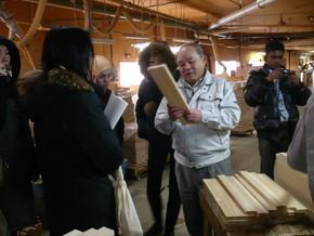 同社の工場にて、ひのき材を手に説明される中西社長と説明に聞き入る研修員。