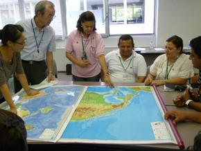 大きな世界地図を前に研修員がそれぞれ生立ち、職歴を説明しました。良いチーム作りのためのアイスブレーキングです。