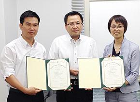 研修修了証を手にするテクノグローバル(株)高田弘之代表取締役(中央)、クオンさん(左)、PREX 瀬戸口(右)。