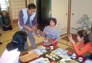 農家民宿での郷土料理体験中。食した椎茸の原木の説明を受ける。