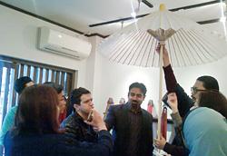京和傘の構造についての説明を受ける研修員。